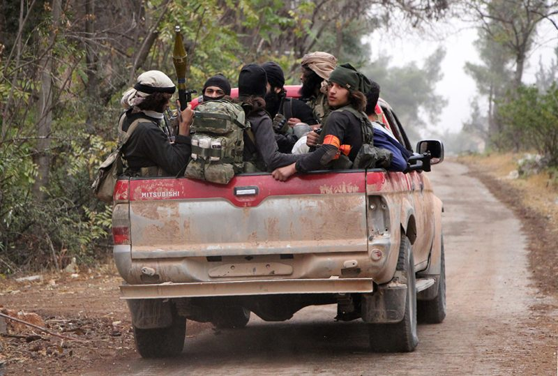 Rebel fighters from the Jaish al-Fatah (or Army of Conquest) brigades sit in the back of a truck as they take part in a major assault on Syrian government forces West of Aleppo city on October 28, 2016.Syrian opposition fighters launched a major assault on government forces to break a months-long siege of rebel-held neighbourhoods of the battered city of Aleppo. Rebel groups including the powerful Ahrar al-Sham faction and former Al-Qaeda affiliate Fateh al-Sham Front fired waves of rockets into government-held western Aleppo, killing at least 15 civilians, a monitor said. The rebels also targeted government positions east of Aleppo city and in the coastal province of Latakia. / AFP PHOTO / Omar haj kadour