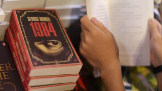 A boy reads a book next to copies of British writer George Orwell's 1984 at Hong Kong's annual book fair on July 15, 2015. The 26th edition of the fair showcased a record number of over 580 exhibitors from 33 countries and regions. AFP PHOTO / Aaron Tam / AFP PHOTO / aaron tam