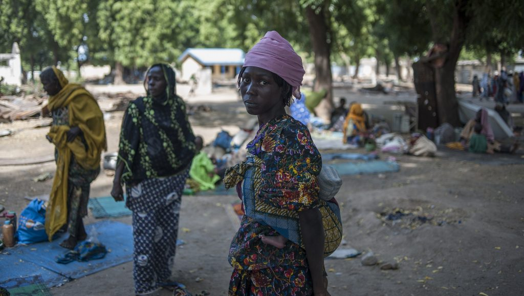 A woman and her baby wait to be integrated into the Internally Displaced People (IDP) camp, in Bama, on December 8, 2016 upon their arrival. The houses are burnt-out shells, and charred cars and petrol pumps line the roads in the once-bustling Nigerian trade hub of Bama before it was razed by Boko Haram jihadists, know 85% is destroyed. The camp now houses a little over 10,000 people who either escaped or survived the seven months under Boko Haram rule. The conflict with Boko Haram in northeast Nigeria has displaced more than 2.6 million people. / AFP PHOTO / STEFAN HEUNIS