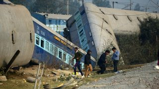 Indian officials and bystanders gather at the derailed train carriages at Rura, some 30 kms west of Kanpur on December 28, 2016, following a train crash in the northern Indian state of Uttar Pradesh.  At least two people died and 28 were injured after a train derailed in north India, close to the site of a previous rail accident that killed 146. / AFP PHOTO / Sanjay KANOJIA