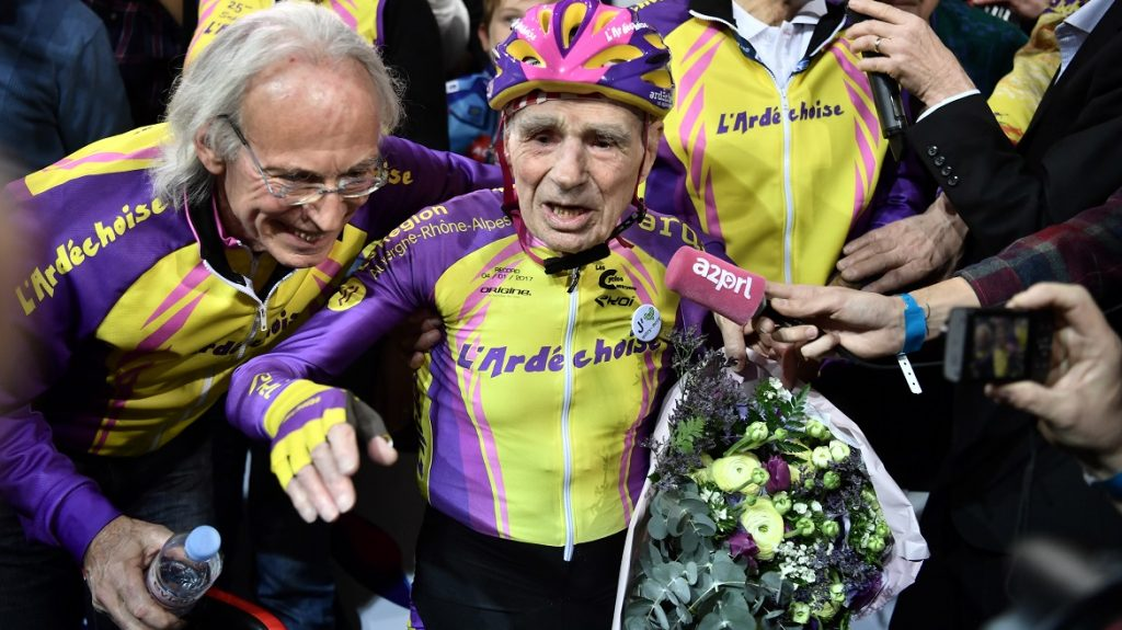 French centenarian cyclist Robert Marchand, 105 (C) reacts after setting a one-hour track cycling World record in the over-105 age group at 22.547m, at the Saint-Quentin-en-Yvelines race track on January 4, 2017.  / AFP PHOTO / PHILIPPE LOPEZ