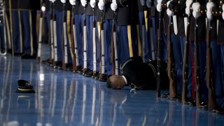 A member of the US Army Honor Guard lays on the floor after passing out during an Armed Forces Full Honor Farewell Review for US President Barack Obama at Joint Base Myer-Henderson in Arlington, Virginia, January 4, 2017. / AFP PHOTO / JIM WATSON