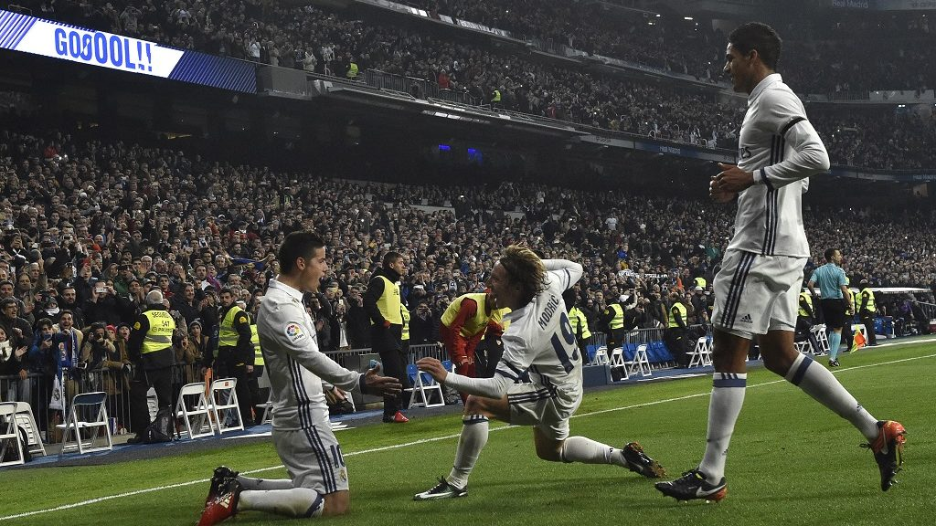 Real Madrid's Colombian midfielder James Rodriguez (L) celebrates with Real Madrid's Croatian midfielder Luka Modric (C) and Real Madrid's French defender Raphael Varane after scoring on a penalty kick during the Spanish Copa del Rey (King's Cup) round of 16 first leg football match Real Madrid CF vs Sevilla FC at the Santiago Bernabeu stadium in Madrid on January 4, 2017. / AFP PHOTO / GERARD JULIEN