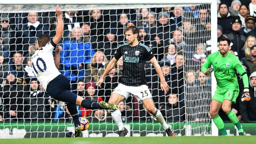 Tottenham Hotspur's English striker Harry Kane (L) scores his team's third goal during the English Premier League football match between Tottenham Hotspur and West Bromwich Albion at White Hart Lane in London, on January 14, 2017. / AFP PHOTO / Glyn KIRK / RESTRICTED TO EDITORIAL USE. No use with unauthorized audio, video, data, fixture lists, club/league logos or 'live' services. Online in-match use limited to 75 images, no video emulation. No use in betting, games or single club/league/player publications.  /