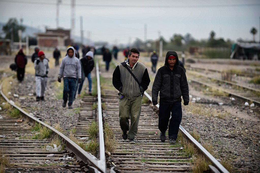 Migrants walk along the train tracks in the community of Caborca in Sonora state, Mexico, on January 13, 2017.