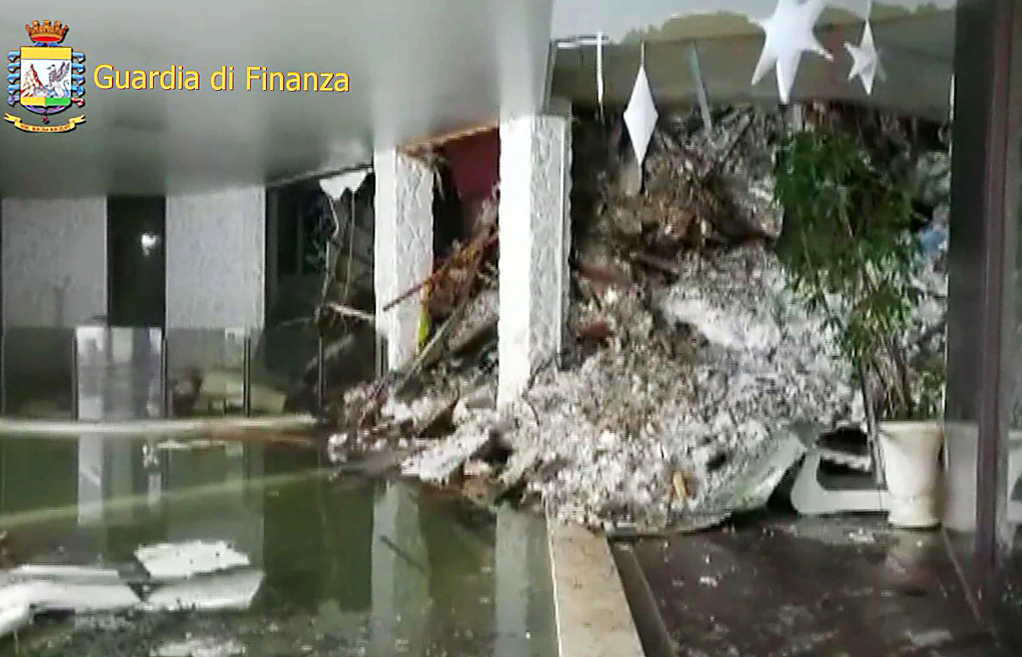 "This image grab made from a video handout released by the Guardia di Finanza on January 19, 2017 shows a wall of snow engulfing the inside of the Hotel Rigopiano, near the village of Farindola, on the eastern lower slopes of the Gran Sasso mountain. Up to 30 people were feared to have died after an Italian mountain Hotel Rigopiano was engulfed by a powerful avalanche in the earthquake-ravaged centre of the country. Italy's Civil Protection agency confirmed the Hotel Rigopiano had been engulfed by a two-metre (six-feet) high wall of snow and that emergency services were struggling to get ambulances and diggers to the site. / AFP PHOTO / Guardia di Finanza press office / Handout / RESTRICTED TO EDITORIAL USE - MANDATORY CREDIT ""AFP PHOTO / GUARDIA DI FINANZA "" - NO MARKETING NO ADVERTISING CAMPAIGNS - DISTRIBUTED AS A SERVICE TO CLIENTS"