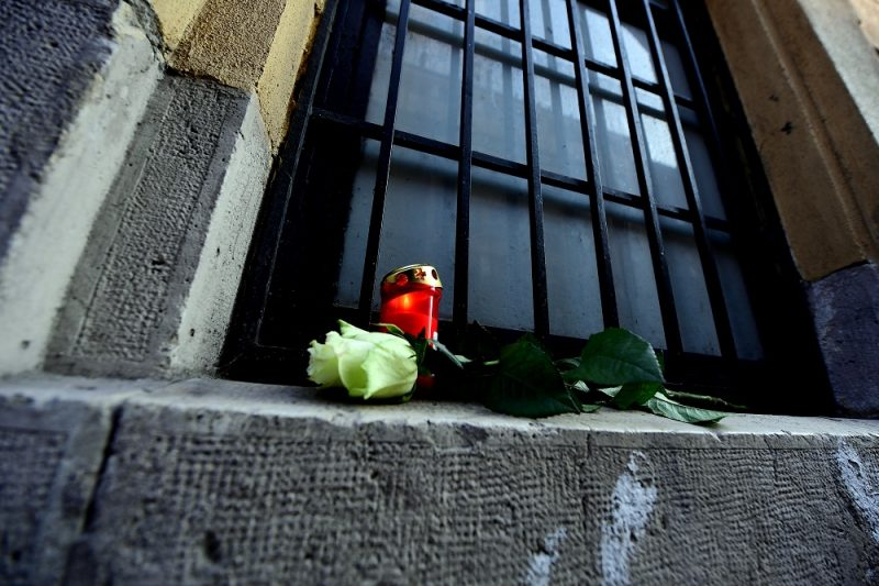 Candles and flowers are placed in a window of the Szinyei Merse Pal high school in Budapest on January 21, 2017, to commemorate victims of a bus accident in Italy. A coach carrying Hungarian teenagers home from a school trip crashed and burst into flames on a motorway in northern Italy, killing 16 people, firefighters said. Some 39 injured were taken to hospital following the accident near Verona, which occurred when the vehicle smashed into a bridge pillar, according to emergency workers.  / AFP PHOTO / ATTILA KISBENEDEK