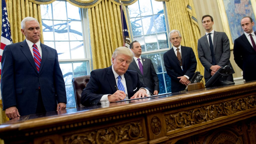 US President Donald Trump signs an executive order in the Oval Office of the White House in Washington, DC, January 23, 2017. Trump on Monday signed three orders on withdrawing the US from the Trans-Pacific Partnership trade deal, freezing the hiring of federal workers and hitting foreign NGOs that help with abortion. / AFP PHOTO / SAUL LOEB