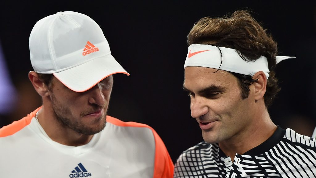 Germany's Mischa Zverev (L) talks to Switzerland's Roger Federer after Federer won their men's singles quarter-final match on day nine of the Australian Open tennis tournament in Melbourne on January 24, 2017. / AFP PHOTO / PAUL CROCK / IMAGE RESTRICTED TO EDITORIAL USE - STRICTLY NO COMMERCIAL USE