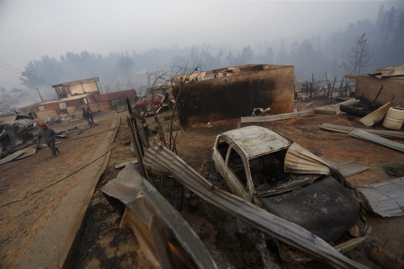 People walk amid the remains of burnt down buildings after a forest fire in Santa Olga, 240 kilometres south of Santiago, on January 26, 2017.  Six people -- among them four firefighters and two police -- have now been killed battling vast forest fires in central Chile, officials said Wednesday. Multiple blazes have ravaged 238,000 hectares (588,000 acres) and are growing, the National Forestry Corporation said in a statement. / AFP PHOTO / PABLO VERA LISPERGUER