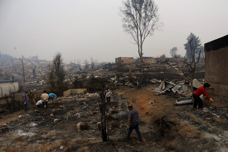 People work to clean up the debris after a forest fire devastated Santa Olga, 240 kilometres south of Santiago, on January 26, 2017.  Six people -- among them four firefighters and two police -- have now been killed battling vast forest fires in central Chile, officials said Wednesday. Multiple blazes have ravaged 238,000 hectares (588,000 acres) and are growing, the National Forestry Corporation said in a statement.   / AFP PHOTO / PABLO VERA LISPERGUER