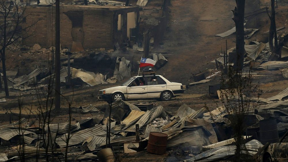 A car with a Chilean flag drives through the debris after a forest fire devastated Santa Olga, 240 kilometres south of Santiago, on January 26, 2017.  Six people -- among them four firefighters and two police -- have now been killed battling vast forest fires in central Chile, officials said Wednesday. Multiple blazes have ravaged 238,000 hectares (588,000 acres) and are growing, the National Forestry Corporation said in a statement.   / AFP PHOTO / PABLO VERA LISPERGUER