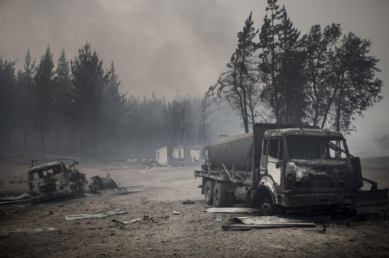 View of the town of Santa Olga, which was destroyed by a forest fire, 330 km south of Santiago, on January 26, 2017.  Six people -- among them four firefighters and two police -- have now been killed battling vast forest fires in central Chile, officials said Wednesday. Multiple blazes have ravaged 238,000 hectares (588,000 acres) and are growing, the National Forestry Corporation said in a statement. / AFP PHOTO / MARTIN BERNETTI