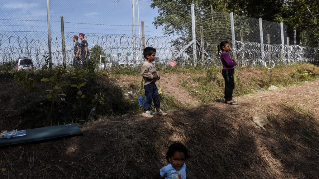 Children stand next to a border fence at a makeshift refugee camp on the Serbian side of the border with Hungary near the town of Horgos on September 18, 2015. Road and rail routes to northern Europe from the Balkans were closing to migrants, after a string of countries shuttered their borders to the relentless human wave. The massive influx, challenging the EU's humanitarian reputation and its vaunted policy of border mobility, has triggered an emergency summit of the 28-nation bloc next week. AFP PHOTO / ARMEND NIMANI / AFP PHOTO / ARMEND NIMANI