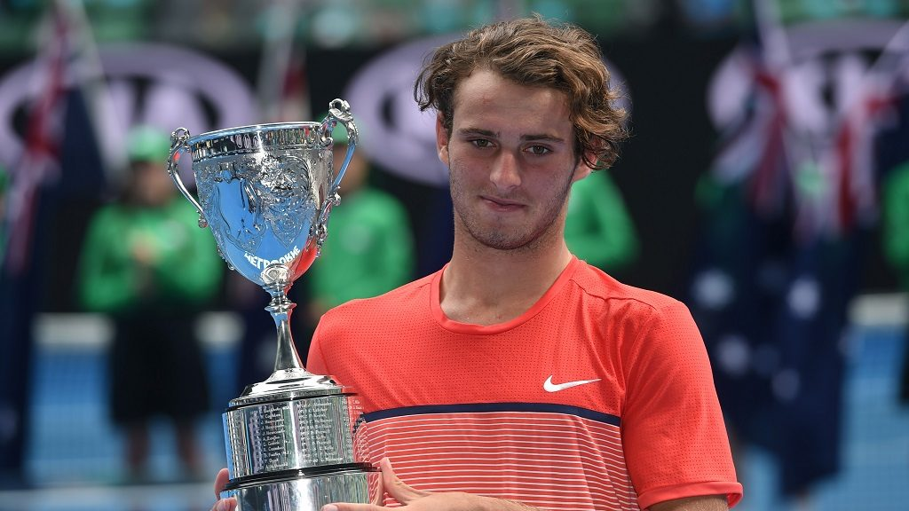 Australia's Oliver Anderson poses with the trophy after victory in his boys singles final match against Uzbekistan's Jurabeck Karimov on day thirteen of the 2016 Australian Open tennis tournament in Melbourne on January 30, 2016. AFP PHOTO / WILLIAM WEST-- IMAGE RESTRICTED TO EDITORIAL USE - STRICTLY NO COMMERCIAL USE / AFP PHOTO / WILLIAM WEST