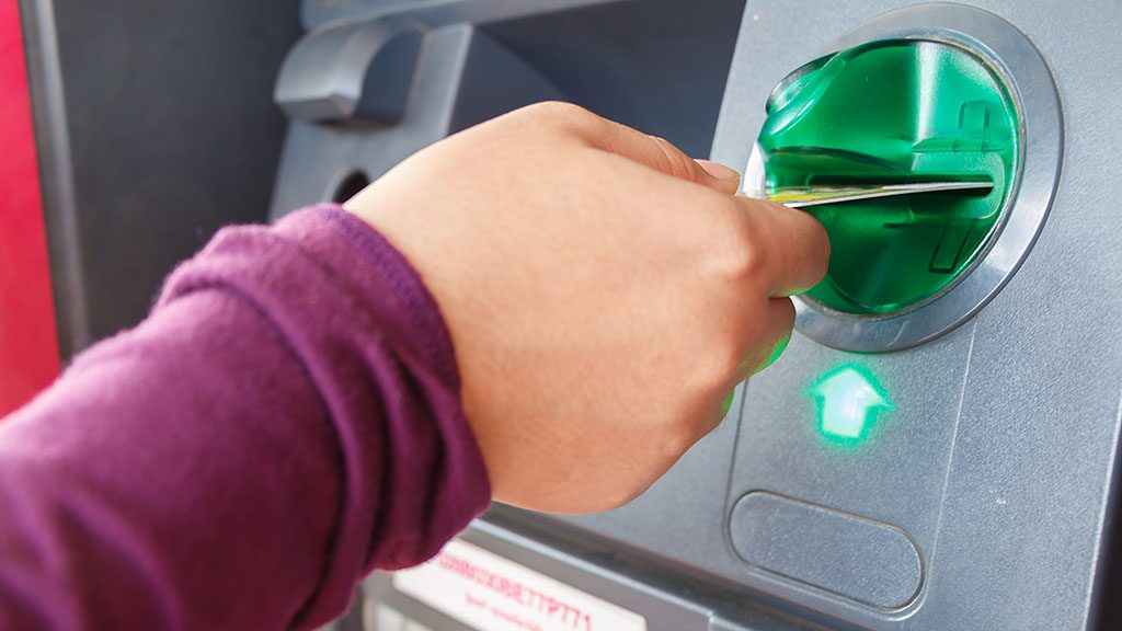 ATM close-up with woman hand
