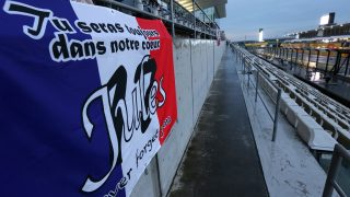 A flag for late Marussia driver Jules Bianchi of France is put up at the grand stand ahead of the Formula One Japanese Grand Prix in Suzuka on September 24, 2015.  AFP PHOTO/YURIKO NAKAO / AFP PHOTO / YURIKO NAKAO