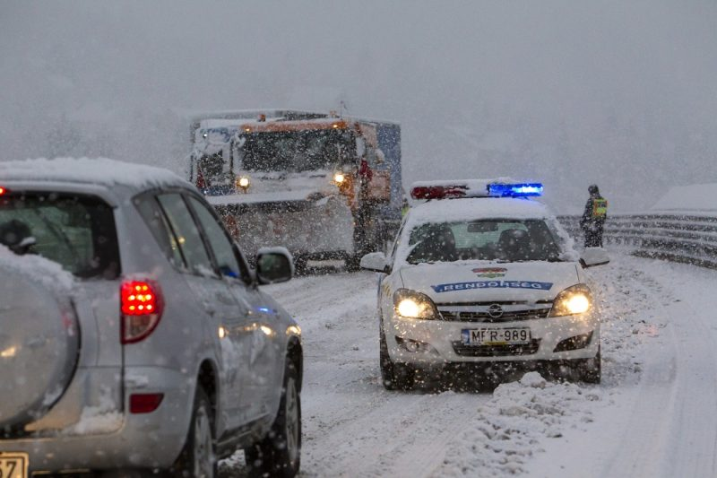 Nagykanizsa, 2017. január 13. Rendõrök állítják meg a forgalmat a sûrû hóesésben a 61-es úton Nagykanizsánál, ahol sószóró dolgozik, mert jármûvek akadtak el 2017. január 13-án. MTI Fotó: Varga György