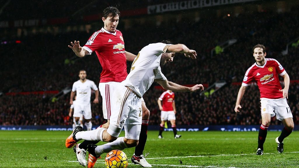 Angel Rangel of Swansea City goes over from a challenge by Matteo Darmian of Manchester United and was booked for an alleged dive during the Barclays Premier League match between Manchester United and Swansea City played at Old Trafford, Manchester on January 2nd 2016 - Photo Matt West / BPI / DPPI