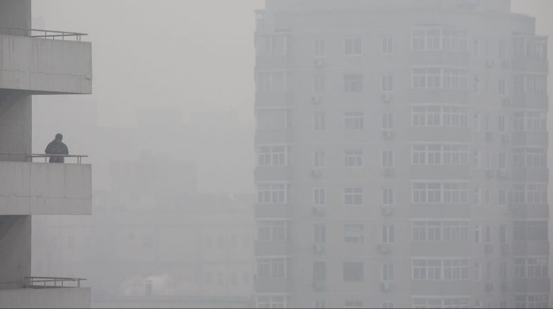 A man stands on a balcony as buildings stand shrouded in haze in Beijing, China, on Monday, Nov. 30, 2015. The round of air pollution that began last week is the heaviest of 2015, the Beijing environmental protection bureau said on its official microblog Tuesday. Photographer: Qilai Shen/Bloomberg via Getty Images