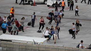 FORT LAUDERDALE, FL - JANUARY 06: People seek cover on the tarmac of Fort Lauderdale-Hollywood International airport after a shooting took place near the baggage claim on January 6, 2017 in Fort Lauderdale, Florida. Officials are reporting that five people were killed and eight wounded in an attack by a single gunman.   (Photo by Joe Raedle/Getty Images)