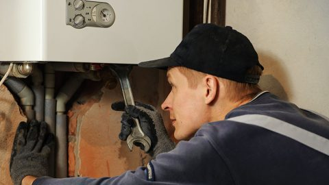 Man connects the gas boiler to the pipes with a wrench