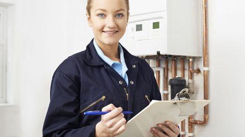 57482889 - female plumber working on central heating boiler