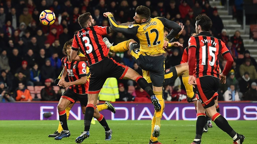 Arsenal's French striker Olivier Giroud (centre right) scores thier third goal past Bournemouth's English defender Steve Cook during the English Premier League football match between Bournemouth and Arsenal at the Vitality Stadium in Bournemouth, southern England on January 3, 2017. The game finished 3-3. / AFP PHOTO / Glyn KIRK / RESTRICTED TO EDITORIAL USE. No use with unauthorized audio, video, data, fixture lists, club/league logos or 'live' services. Online in-match use limited to 75 images, no video emulation. No use in betting, games or single club/league/player publications.  /