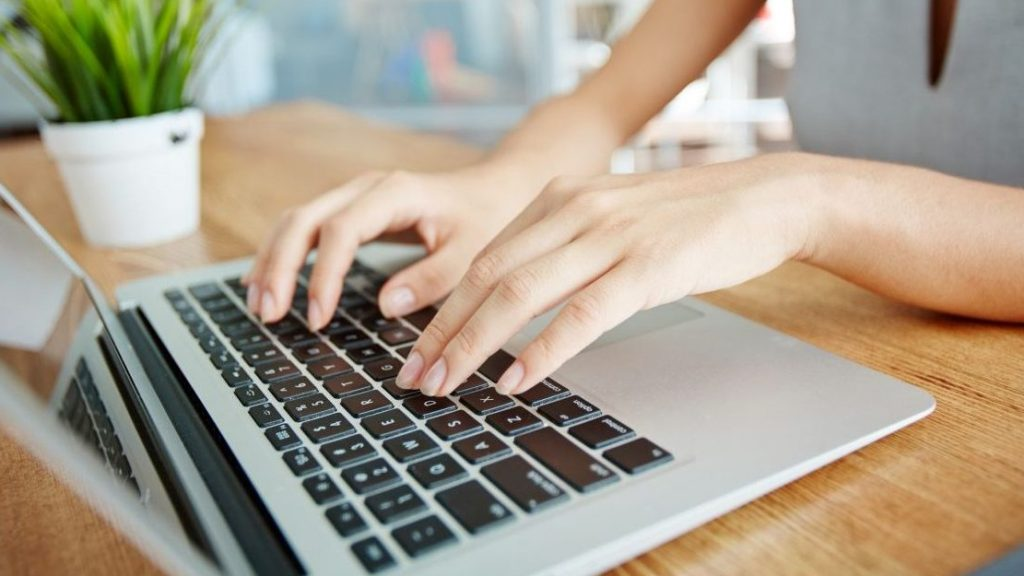 Close-up of femeal hands typing on laptop