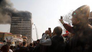 Teherán, 2017. január 19. A lángokban álló Plasco toronyház oltásáról készítenek felvételt járókelõk Teheránban 2017. január 19-én, miután egyelõre ismeretlen okból tûz ütött ki az épületben, amelynek felsõ szintjei beomlottak. Az iráni állami televízió szerint a felhõkarcolóban rekedt emberek és a tûzoltók közül többen életüket vesztették, legkevesebb 38-an megsérültek. (MTI/EPA/Abedin Taherkenareh)