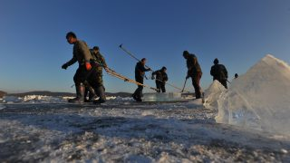 Chinese workers collect ice blocks on the frozen Xiuhu Lake in Qipan Mountain in Shenyang city, northeast China's Liaoning province, 4 January 2017.  Chinese workers collected ice blocks from the frozen Xiuhu Lake in Qipan Mountain in Shenyang city, northeast China's Liaoning province. The ice blocks collected in Liaoning's coastal areas are used for preserving sea food, a practice that dates back 100 years. About 700 ice-collecting devices can create 700,000 ice blocks a day, generating a total output of nearly 200 million yuan ($29 million) in one month.