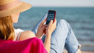 Rear view shot of a woman relaxing on seaside and using her mobile phone while on summer vacation.