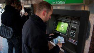A customer holds forint currency notes at an OTP Bank Plc automated teller machine (ATM) in this arranged photograph in Budapest, Hungary, on Saturday, Jan. 7, 2012. Hungary raised its target amount in a sale of bills, paying the highest yield since June 2009 as Prime Minister Viktor Orban's Cabinet worked to restart talks on an international bailout. Photographer: Akos Stiller/Bloomberg via Getty Images