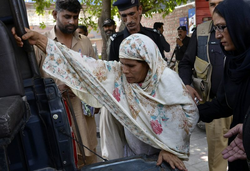 """Pakistani police escort Perveen Bibi (C), who allegedly killed her own daughter by burning her alive, as they go to local court in Lahore on June 10, 2016. Pakistani teenager Zeenat Bibi was burnt alive by her mother on June 8 after marrying a man of her own choice, police said, the latest in a string of so-called """"honour killings"""" in the country. / AFP PHOTO / ARIF ALI"""
