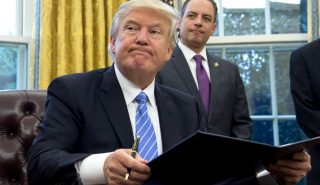 US President Donald Trump signs an executive order as Chief of Staff Reince Priebus looks on in the Oval Office of the White House in Washington, DC, January 23, 2017. Trump on Monday signed three orders on withdrawing the US from the Trans-Pacific Partnership trade deal, freezing the hiring of federal workers and hitting foreign NGOs that help with abortion. / AFP PHOTO / SAUL LOEB