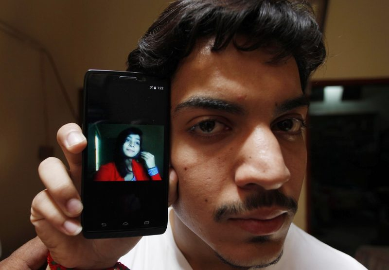 Hassan Khan shows the picture of his wife Zeenat Bibi, who was burnt alive by her mother, on his cellphone at his residence in Lahore on June 8, 2016.  A Pakistani mother burnt her 16-year-old daughter alive for marrying a man of her own choice, before running out into the street to tell neighbours she killed the teenager for dishonouring the family. / AFP PHOTO / STR