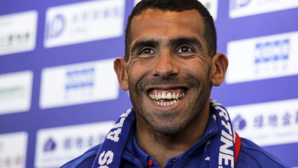 Argentine striker Carlos Tevez smiles during a press conference in Shanghai on January 21, 2017. Tevez held his first press conference for his new club Shanghai Shenhua, which reportedly has made him the world's highest-paid football player. / AFP PHOTO / STR / China OUT