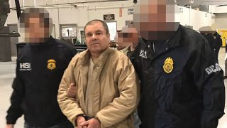 """(FILES) This file handout photo taken on January 19, 2017, released by the Mexican Interior Ministry, shows Joaquin Guzman Loera aka """"El Chapo"""" Guzman (C) escorted in Ciudad Juarez by the Mexican police as he is extradited to the United States.  A US judge on January 25, 2017 has ordered that Mexican drug lord Joaquin """"El Chapo"""" Guzman appear by video link at his next court hearing to avoid unnecessary transfers for one of the world's most notorious criminals. The 59-year-old Guzman, accused of running one of the world's biggest ever drug empires, was extradited to the United States on January 19 after twice escaping from prison in Mexico.  / AFP PHOTO / Mexican Interior Ministry / HO /   RESTRICTED TO EDITORIAL USE-MANDATORY CREDIT """"AFP PHOTO/INTERIOR MINISTRY OF MEXICO"""" NO MARKETING NO ADVERTISING CAMPAIGNS-DISTRIBUTED AS A SERVICE TO CLIENTS-XGTY"""