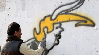 An Iraqi graffiti artist sprays a cement wall with anti-US President Donald Trump slogans in the southern Iraqi city of Basra on February 2, 2017. / AFP PHOTO / HAIDAR MOHAMMED ALI