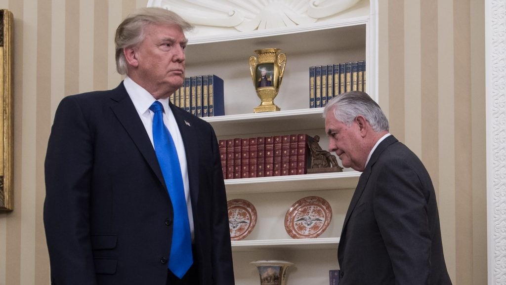 US President Donald Trump (L) stands as Secretary of State Rex Tillerson walks into the Oval Office at the White House to be sworn in in Washington, DC, on February 1, 2017. President Trump notched a victory with confirmation of Rex Tillerson as his secretary of state, but opposition Democrats girded for battle over several other nominations, including his pick for the US Supreme Court. / AFP PHOTO / NICHOLAS KAMM