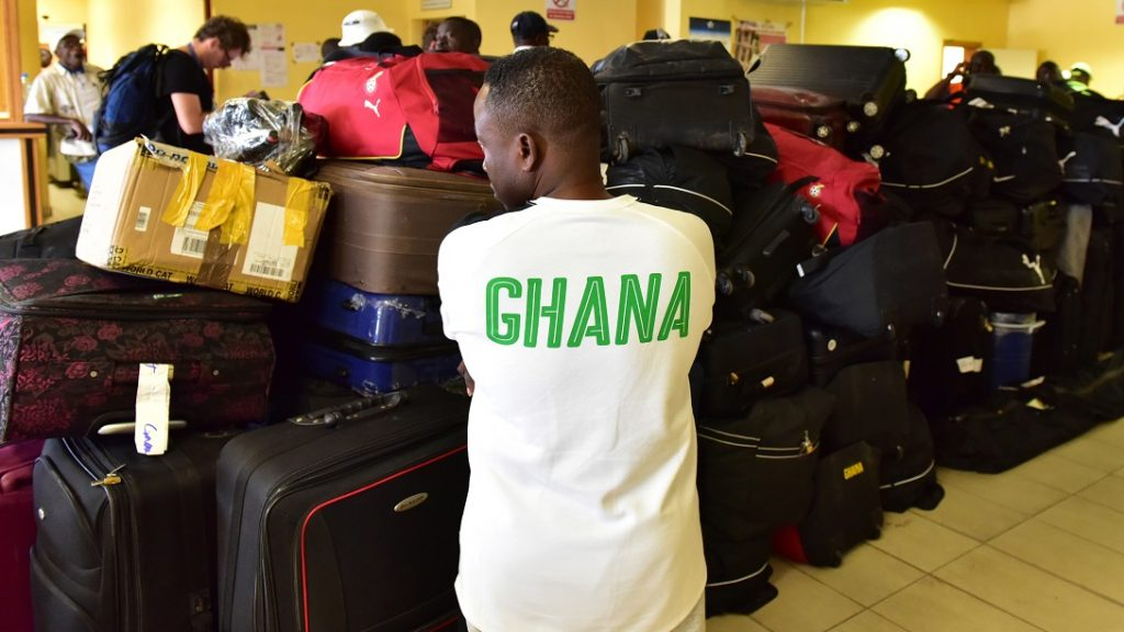 """A man wearing a tee shirt on which is written """"Ghana"""" on the back, stands next to the pile of suitcases belonging to Ghana's national football team players and officials, at the airport in Franceville, on February 3, 2017, as they leave after defeat against Cameroon during the semi final football match of the 2017 Africa Cup of Nations football tournament. / AFP PHOTO / ISSOUF SANOGO"""