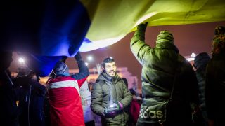 A man uses a flashlight to help others who spread a large Romanian flag  during a rally against the government, in Victory Square in Bucharest, Romania,on February 9, 2016.  / AFP PHOTO / ANDREI PUNGOVSCHI