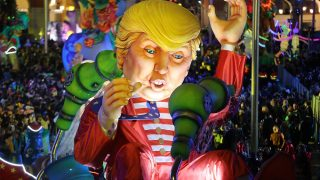 """People look at the float """"Wind of Change"""" depicting US President Donald Trump as it parades in the streets of Nice for the 133rd edition of the Nice Carnival on February 11, 2017 in Nice, southeastern France. The Nice carnival runs until February 25, 2017 under the theme """"The King of Energies"""". / AFP PHOTO / VALERY HACHE"""