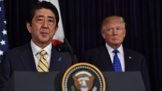 Japanese Prime Minister Shinzo Abe (L) and US President Donald Trump speak at Trump's Mar-a-Lago resort in Palm Beach, Florida, on February 11, 2017, after North Korea reportedly fired a ballistic missile, the first since Donald Trump became US president. / AFP PHOTO / Nicholas Kamm