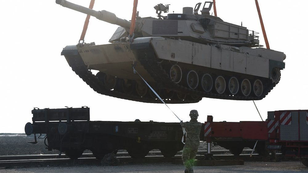 """A US soldier helps to manoever a tank from a railway car as US Army personnel offload military equipment at the Mihail Kogalniceanu Air Base near Constanta in Romania on February 14, 2017. Soldiers and equipment from the 3rd Armored Brigade Combat Team, 4th Infantry Division, arrived at the Mihail Kogalniceanu Air Base as part of the ongoing Atlantic Resolve mission. The combined arms unit of the """"Fighting Eagles"""" brings a full complement of 500 US troops, a US Army infantry battalion's M1 Abrams tanks, M2 Bradley fighting vehicles, and M109A6 Paladin self-propelled howitzers to Romania. / AFP PHOTO / DANIEL MIHAILESCU"""