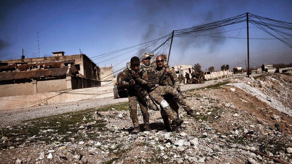 """Members of Iraq's elite Rapid Response Division carry a wounded comrade in the northern city of Mosul, as Iraqi forces continue the offensive to retake the city's western half from Islamic State (IS) group fighters, on February 25, 2017. The west bank of Mosul is where Abu Bakr al-Baghdadi made his only public appearance as IS leader in July 2014 and proclaimed a """"caliphate"""", which at its greatest extent controlled a third of Iraq, but after more than two years of a government fightback it has become the last major jihadist bastion in the country. / AFP PHOTO / ARIS MESSINIS"""
