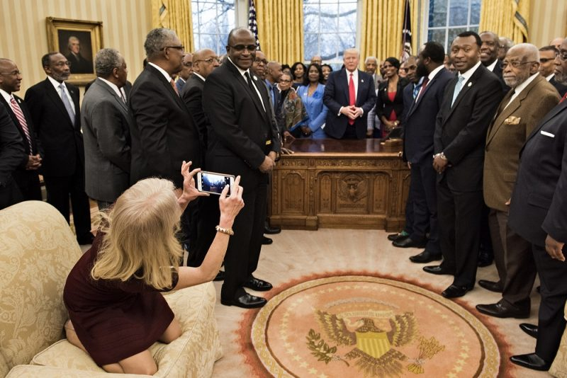 Counselor to the President Kellyanne Conway takes a photo as US President Donald Trump and leaders of historically black universities and colleges talk before a group photo in the Oval Office of the White House before a meeting with US Vice President Mike Pence February 27, 2017 in Washington, DC. / AFP PHOTO / Brendan Smialowski