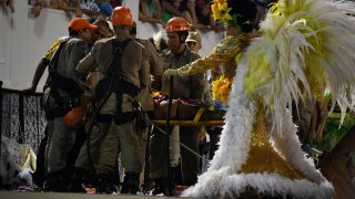 Firefighters assist a reveller of the Unidos da Tijuca samba school after the third floor of an allegorical car collapsed during the second night of Rio's Carnival at the Sambadrome in Rio de Janeiro, Brazil, early on February 28, 2017. / AFP PHOTO / Vanderlei ALMEIDA