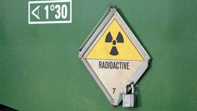 """A picture taken on November 22, 2011 shows a radioactivity warning symbol on a """"CASTOR"""" (Cask for Storage and Transportation of Radioactive Material) container carrying highly radioactive nuclear waste which is part of a convoy waiting at the Areva's train station in Valognes, northwestern France, a day before leaving for Gorleben in Germany. Despite massive police forces deployment, anti-nuclear protests are expected in France and Germany against the transport of the eleven so-called """"CASTORS"""" containing nuclear waste. AFP PHOTO / KENZO TRIBOUILLARD / AFP PHOTO / KENZO TRIBOUILLARD"""