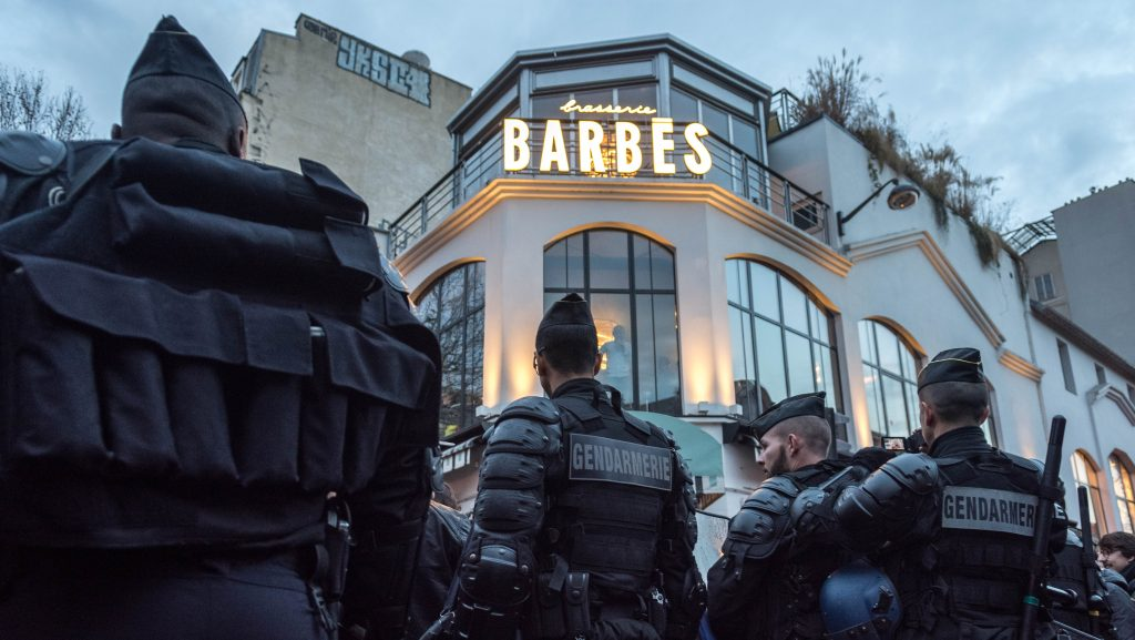 """Anti riot police stands guard as people gather during a demonstration to show support to a 22-year-old youth worker, identified only as Theo, after he was assaulted on February 2, in Barbes Rochechouart district in Paris, on February 15, 2017. French President Francois Hollande called for """"justice"""" over the alleged rape of a black youth with a police baton, an incident that has sparked 10 nights of rioting and more than 200 arrests. (Photo by Julien Mattia/NurPhoto)"""